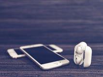 莫斯科,俄罗斯- 2017年12月19日:白色iPhone、无线AirPods耳机和开放箱子给的耳机充电 图库摄影
