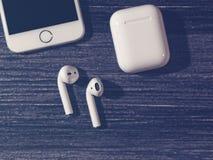 莫斯科,俄罗斯- 2017年12月19日:白色iPhone、无线AirPods耳机和箱子给的耳机充电 图库摄影