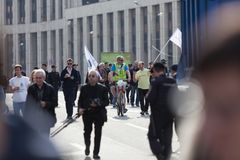 莫斯科,俄罗斯- 2018年4月30日:负担商标` H `的自行车的一个人Navalny商标在萨哈罗夫大道的一次集会以后 免版税图库摄影