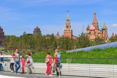 莫斯科,俄罗斯- 2018年6月03日:走的游人在Zaryadye在克里姆林宫和圣蓬蒿` s大教堂背景停放  免版税库存图片