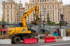莫斯科,俄罗斯- 2017年10月24日:黄色轮子挖掘机现代,运转在城市环境里在旅馆`乌克兰`旁边 库存照片