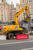 莫斯科,俄罗斯- 2017年10月24日:黄色轮子挖掘机现代,运转在城市环境里在旅馆`乌克兰`旁边 免版税库存照片