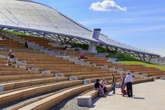 莫斯科,俄罗斯- 2018年6月03日:游人坐在大圆形露天剧场的一条长凳在Zaryadye公园在一个晴朗的夏天早晨 免版税库存照片