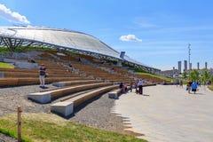 莫斯科,俄罗斯- 2018年6月03日:游人坐在大圆形露天剧场的一条长凳在Zaryadye公园在一个晴朗的夏天早晨 免版税库存图片