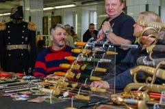 莫斯科,俄罗斯- 2017年3月19日:古色古香的剑和匕首的卖主等待买家在市场 库存照片