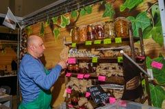 莫斯科,俄罗斯- 2017年2月25日:国产品的烂醉如泥的蘑菇的卖主在市场的在买家的一个瓶子投入 库存图片