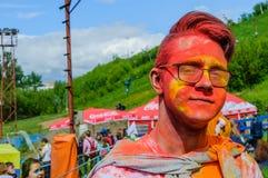 莫斯科,俄罗斯- 2017年6月3日:少年男孩佩带的玻璃特写镜头画象与面孔的在Holi表示以后的油漆 免版税库存照片