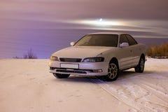 莫斯科,俄罗斯7月10日2018年:在柏油路的白色汽车丰田标记2逗留在雪在莫斯科在晚上 免版税库存照片