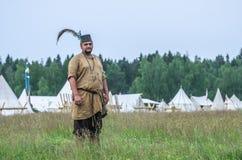 莫斯科,俄罗斯6月06,2016 :古老农民服装的人在草的绿色领域站立 免版税库存图片