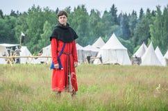 莫斯科,俄罗斯6月06,2016 :古老商人服装的人在草的绿色领域站立 库存照片