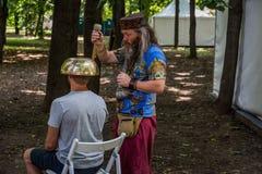 莫斯科,红普列斯尼亚的, 2018年8月05日公园:一个人做与一个大西藏唱歌碗的按摩 免版税库存照片