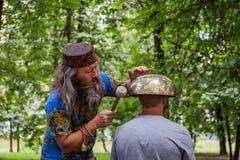 莫斯科,红普列斯尼亚的, 2018年8月05日公园:一个人做与一个大西藏唱歌碗的按摩 免版税库存图片