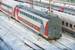 莫斯科, 2月 01日2018年:在俄国铁路旅客列车的对角冬天视图与双重甲板在列车车库教练汽车下 库存照片