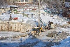 莫斯科, 2月 01日2018年:在肮脏的重型建筑设备,车工作者的冬天视图在工作 在constru的钻操作 库存图片
