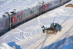 莫斯科, 2月 01日2018年:在铁路旅客长途汽车汽车的冬日视图在雪和冰下在屋顶和维护工作者 字符 免版税库存照片