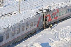 莫斯科, 2月 01日2018年:在铁路旅客长途汽车汽车的冬日视图在雪和冰下在屋顶 高v的维护工作者 免版税库存图片