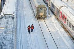 莫斯科, 2月 01日2018年:在铁路维护工作者的冬日视图橙色高可见性背心和旅客列车汽车的 库存图片