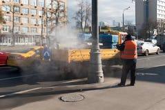 莫斯科10月2017年,俄罗斯 橙色背心的一名工作者象纸和土从路旁柱子 库存照片