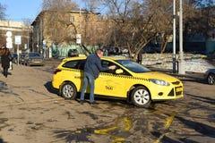 莫斯科- 2015年11月28日:洗涤他的在街道上的出租汽车司机汽车 图库摄影