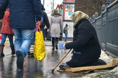 莫斯科1月31日2016年 妇女叫化子用拐棍请求在莫斯科街道上的金钱在冬天 免版税库存照片