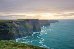 莫赫悬崖用狂放的大西洋方式用美丽的日落和绿松石水 免版税库存图片