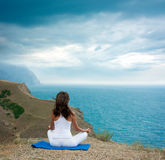 做瑜伽的妇女在海和山 库存图片