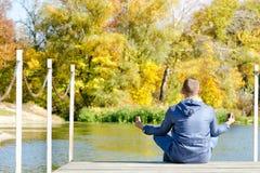 莲花姿势的人坐船坞 秋天,晴朗 回到视图 免版税库存图片