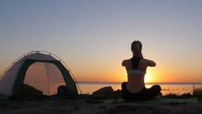 莲花姿势的妇女在日落期间的海滩 影视素材