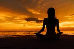 莲花姿势的现出轮廓的妇女在海的背景美好的日落 库存照片