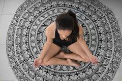 莲花姿势的,在瑜伽席子的上部看法妇女 免版税库存照片