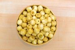 莲花种子莲花坚果,烤和盐溶在木碗,顶视图 图库摄影
