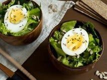 莴苣叶子和鸡蛋沙拉在木碗播种小茴香大面包黑暗背景 库存图片