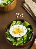 莴苣叶子和鸡蛋沙拉在木碗播种小茴香大面包黑暗背景 免版税库存图片