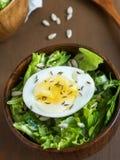 莴苣叶子和鸡蛋沙拉在木碗播种小茴香大面包黑暗背景 库存照片