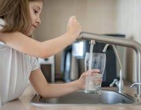 获取一杯轻拍净水的一个小白种人女孩的画象 厨房龙头 逗人喜爱的卷曲孩子 r 免版税库存照片