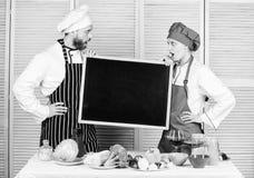 获取技能的范围 拿着空的黑板的男人和妇女夫妇在烹饪学院 主要厨师和预习功课厨师 免版税库存照片