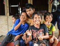 获得一个小组可怜的小男孩和的女孩在照相机前面的乐趣在街道上 免版税库存照片