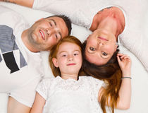 获得一个微笑的家庭说谎在床上的乐趣 免版税库存照片