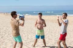 获得三个年轻的人在打排球的海滩的乐趣 图库摄影