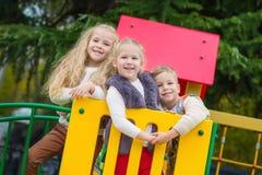 获得三个愉快的孩子乐趣一起 库存图片