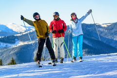 获得三个愉快的滑雪者在冬天滑雪倾斜的乐趣 免版税库存照片