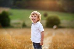获得三的年的小男孩在黄色干草领域的乐趣 免版税图库摄影