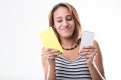 给获得上瘾的女孩打电话与她心爱的智能手机的乐趣 免版税图库摄影