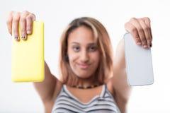 给获得上瘾的女孩打电话与她心爱的智能手机的乐趣 免版税库存图片