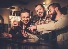 获得与智能手机的乐趣和喝桶装啤酒的老朋友在酒吧柜台在客栈 免版税库存图片