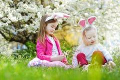 获得两个可爱的妹乐趣在复活节天 免版税库存照片