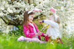 获得两个可爱的妹乐趣在复活节天 免版税图库摄影