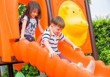 获得两个孩子的朋友乐趣一起使用在儿童` s幻灯片 库存照片
