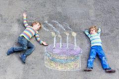 获得两个孩子的男孩与五颜六色的生日蛋糕图画的乐趣与 图库摄影