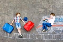 获得两个小孩的男孩与火车图片图画的乐趣与在地面的五颜六色的白垩 免版税库存照片
